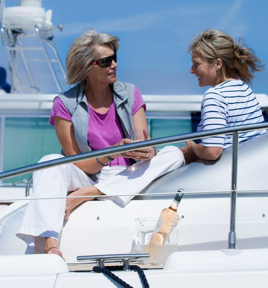 2 ladies chatting on boat (pink t shirt and stripy tshirt) bottle rosy wine near by